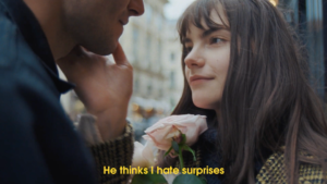 guy giving girl pink rose with subtitles saying He thinks I hate suprises