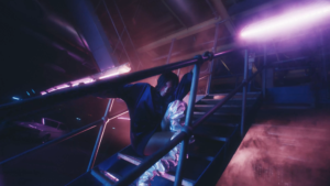 guy on stairs in a dark purple lit room